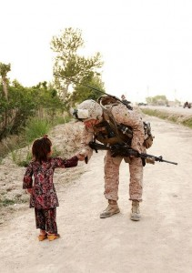 """We want to be good.""  A U.S. Marine stops to shake hands with a young girl while on patrol in Marjah, Afghanistan.  Photo by US Central Command."